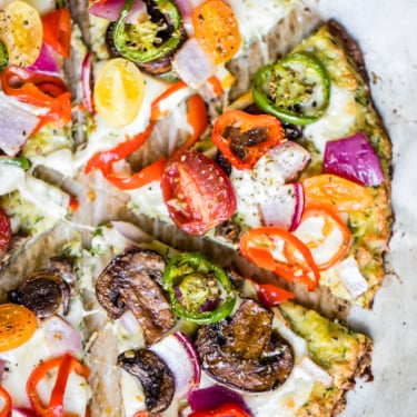 low carb zucchini pizza crust topped with cheese and veggies cut into slices