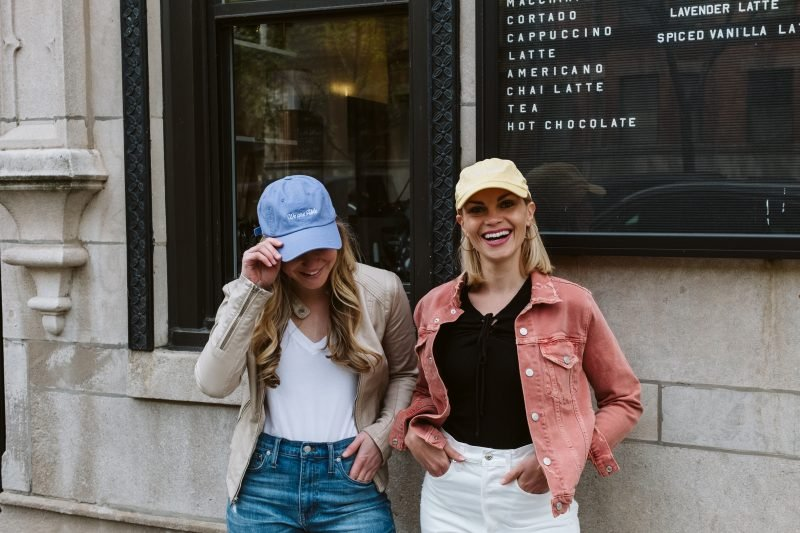 two girls outside of a coffee shop wearing a yellow had and a blue hat