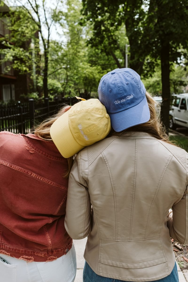 the back of two girls wearing backwards hats