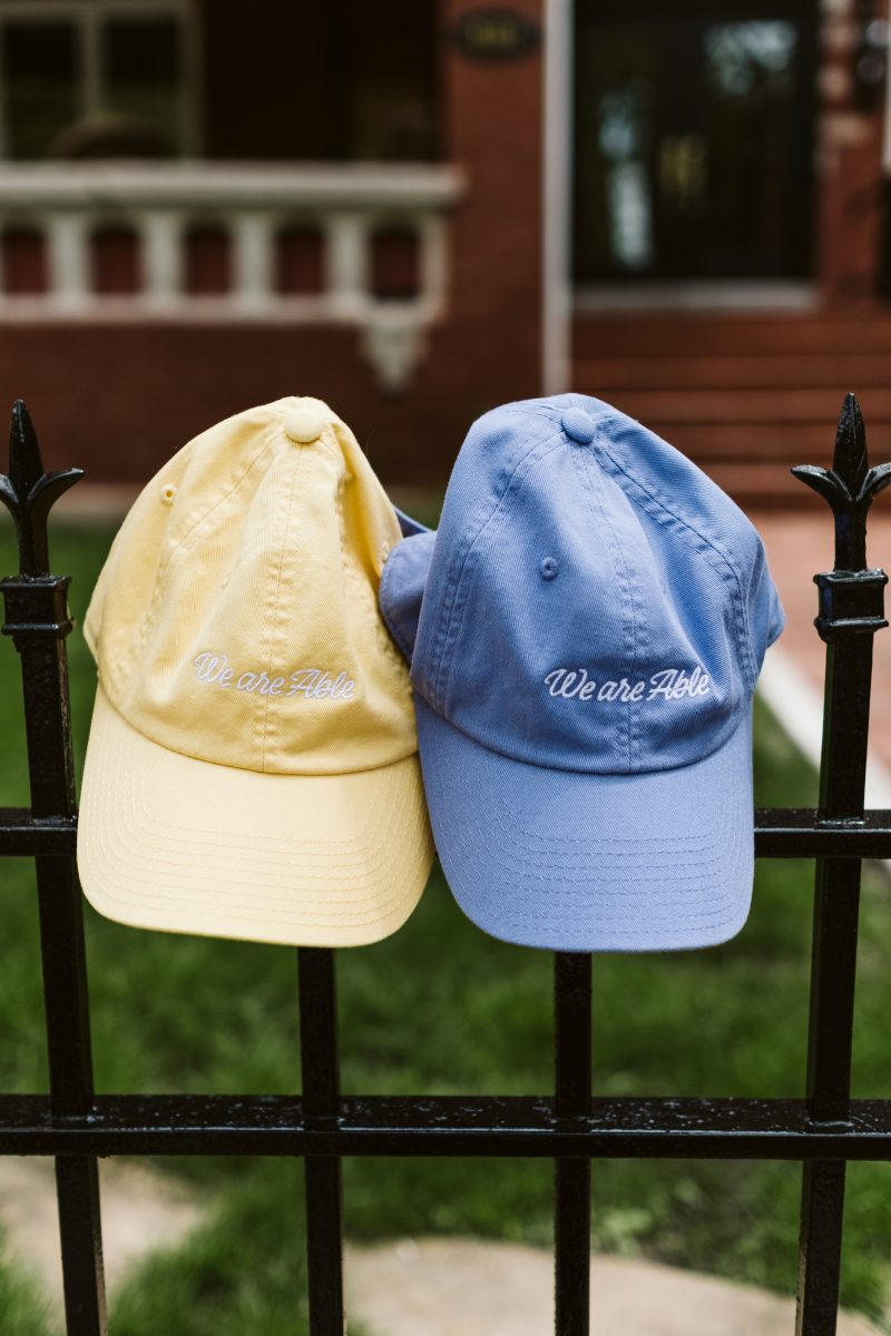 a blue hat and a yellow hat hanging on a fence