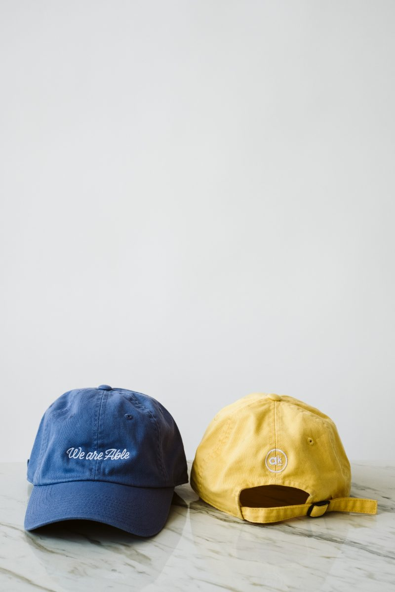 one blue hat and one yellow hat on a marble surface