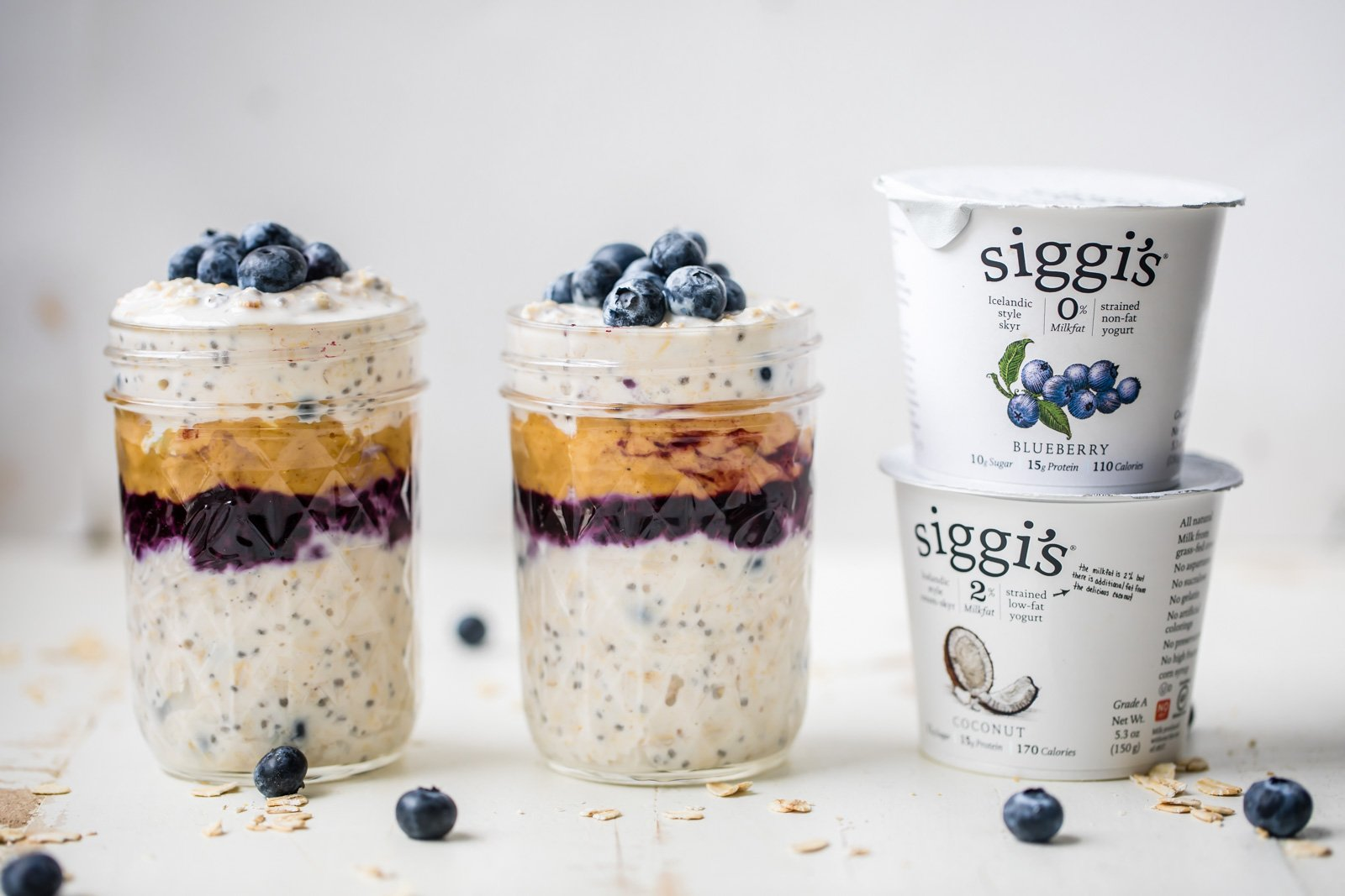 peanut butter blueberry overnight oats in two jars next to two containers of siggi's yogurt