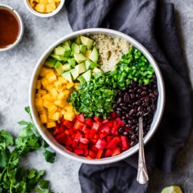 healthy mango black bean quinoa salad in a bowl with a spoon