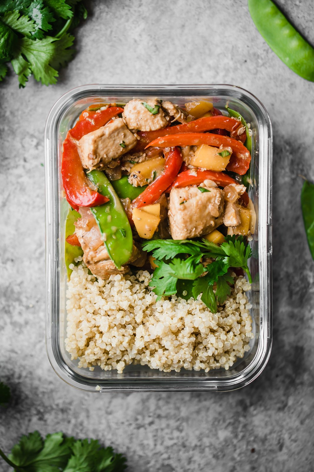 mango chicken stir fry with rice in a glass meal prep container