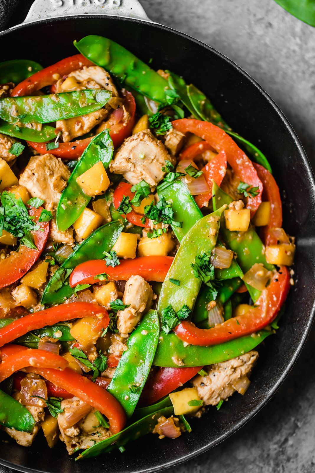 mango chicken stir fry with veggies in a skillet pan