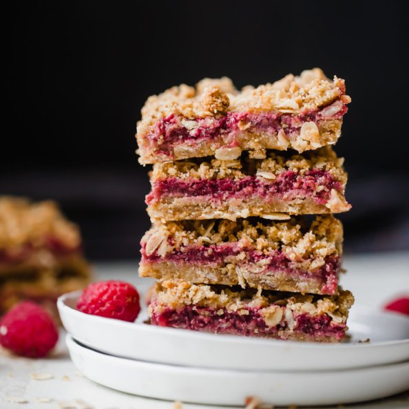 gluten free raspberry crumble bars in a stack on a plate