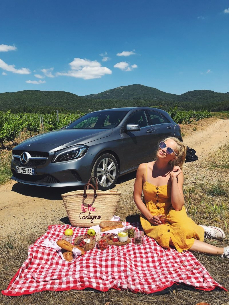 monique sitting on a picnic blanket with a car in the background