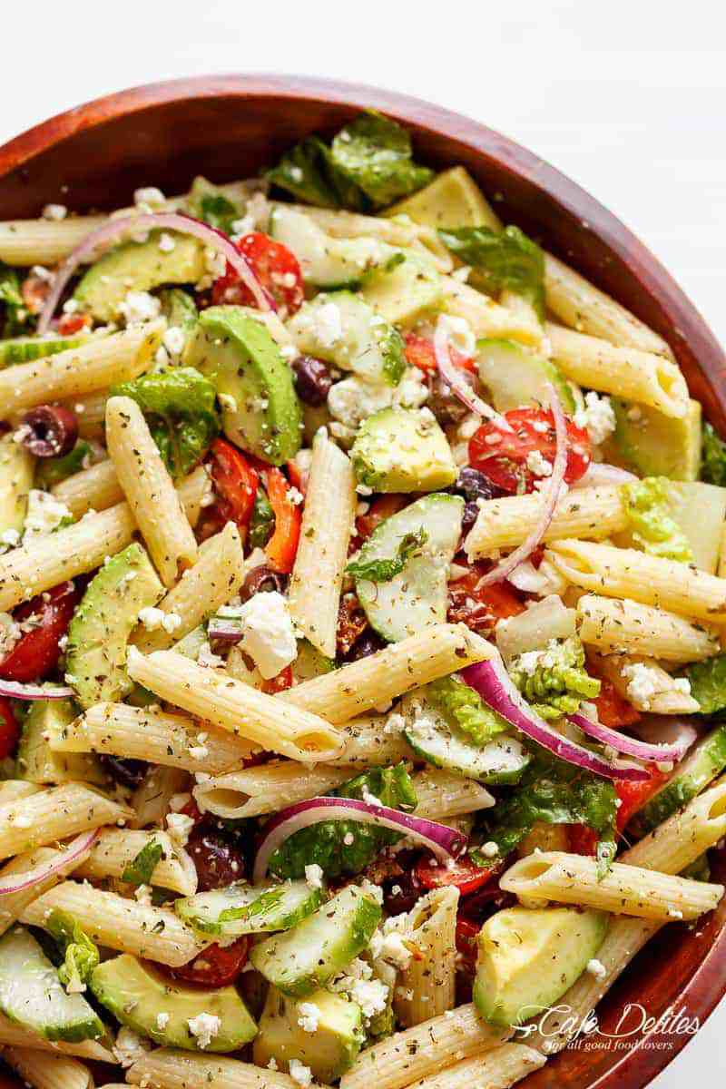 healthy pasta salad recipe in a wooden bowl with avocados, feta, and red onion