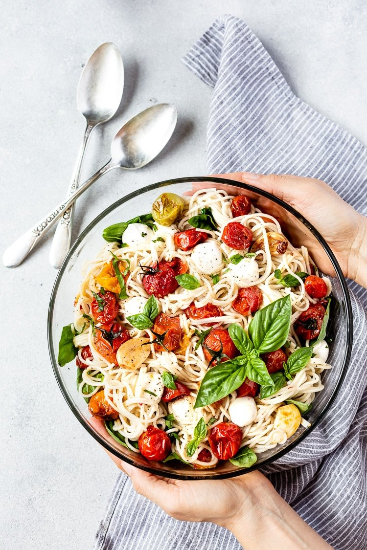 healthy pasta salad recipe in a glass bowl with basil, mozzarella and tomatoes