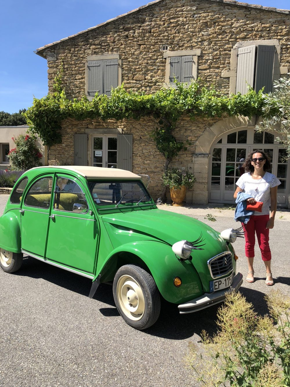 woman standing next to green car next to a stone house