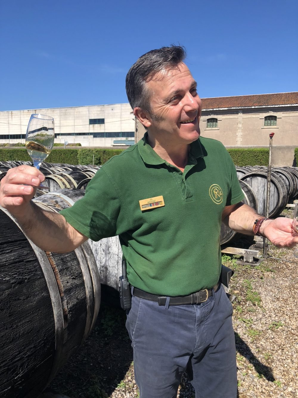 man holding a glass of wine next to wine barrels