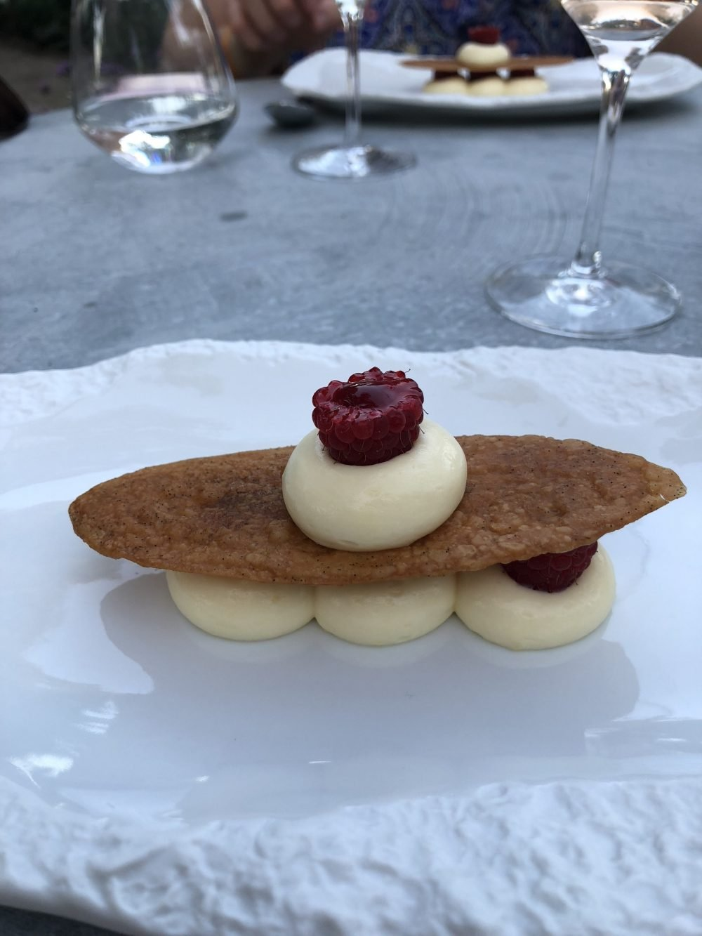 white chocolate mousse with a wafer and raspberries on a plate