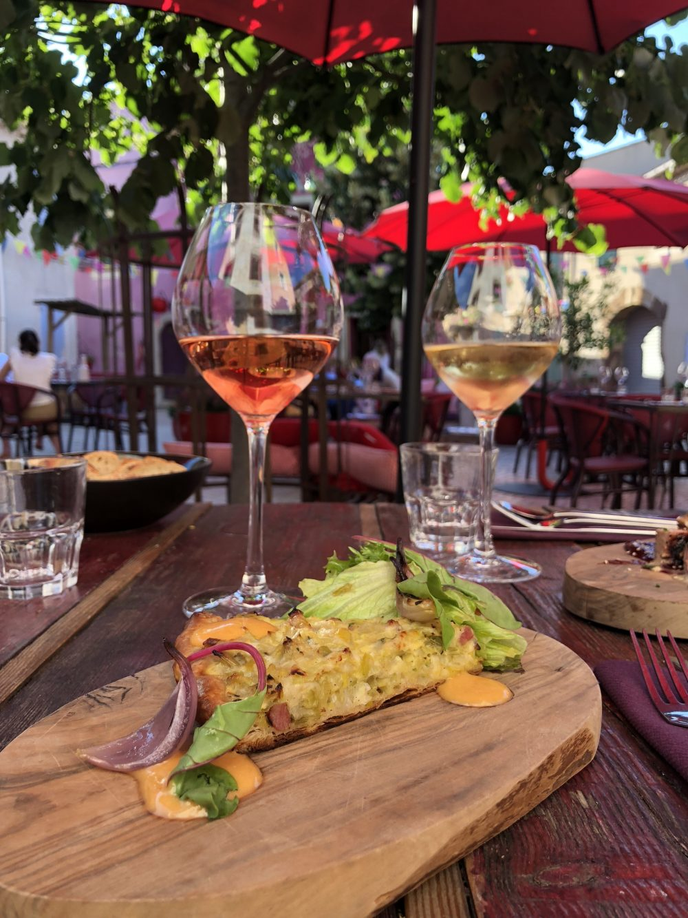 piece of quiche on a wooden board next to glasses of wine