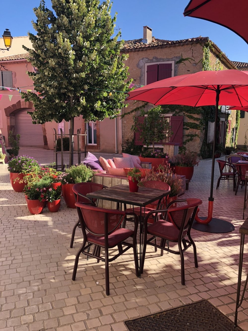 patio with a red umbrella between pink buildings