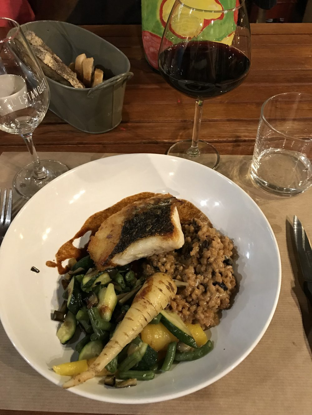 salmon, rice, and vegetables on a plate next to a glass of red wine