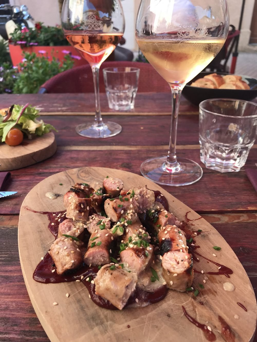 small sausage bites on a wooden board next to glasses of wine
