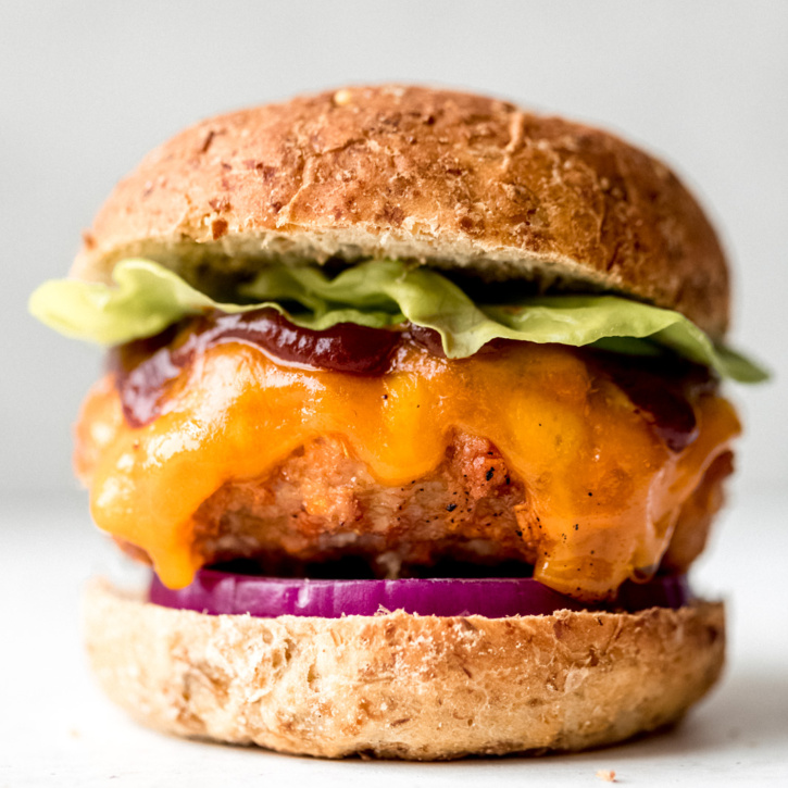 chicken burger topped with lettuce, cheese, and bbq sauce