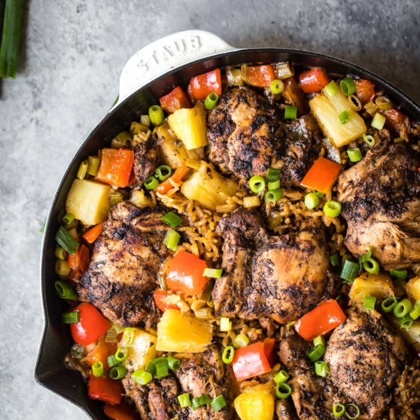 caribbean jerk chicken in a skillet with rice, pineapple, and red peppers