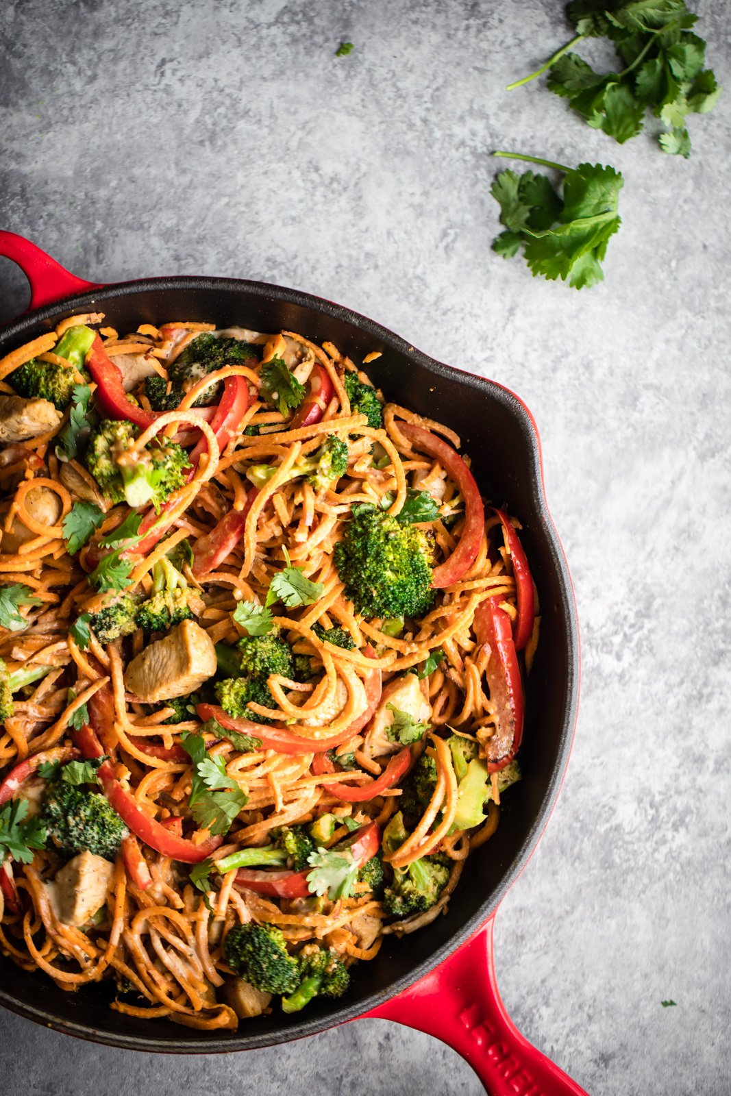spicy thai peanut chicken sweet potato noodle stir fry in a skillet