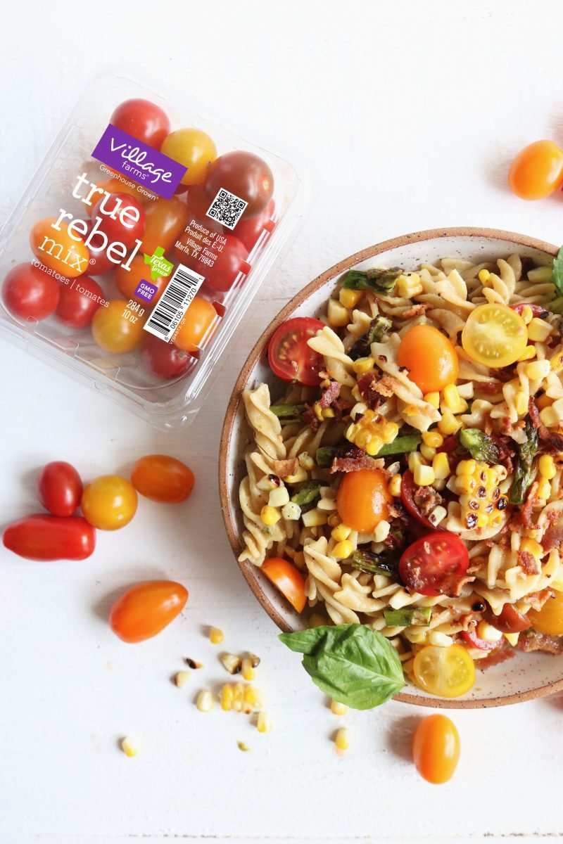 tomato basil healthy pasta salad recipe in a bowl next to a case of cherry tomatoes
