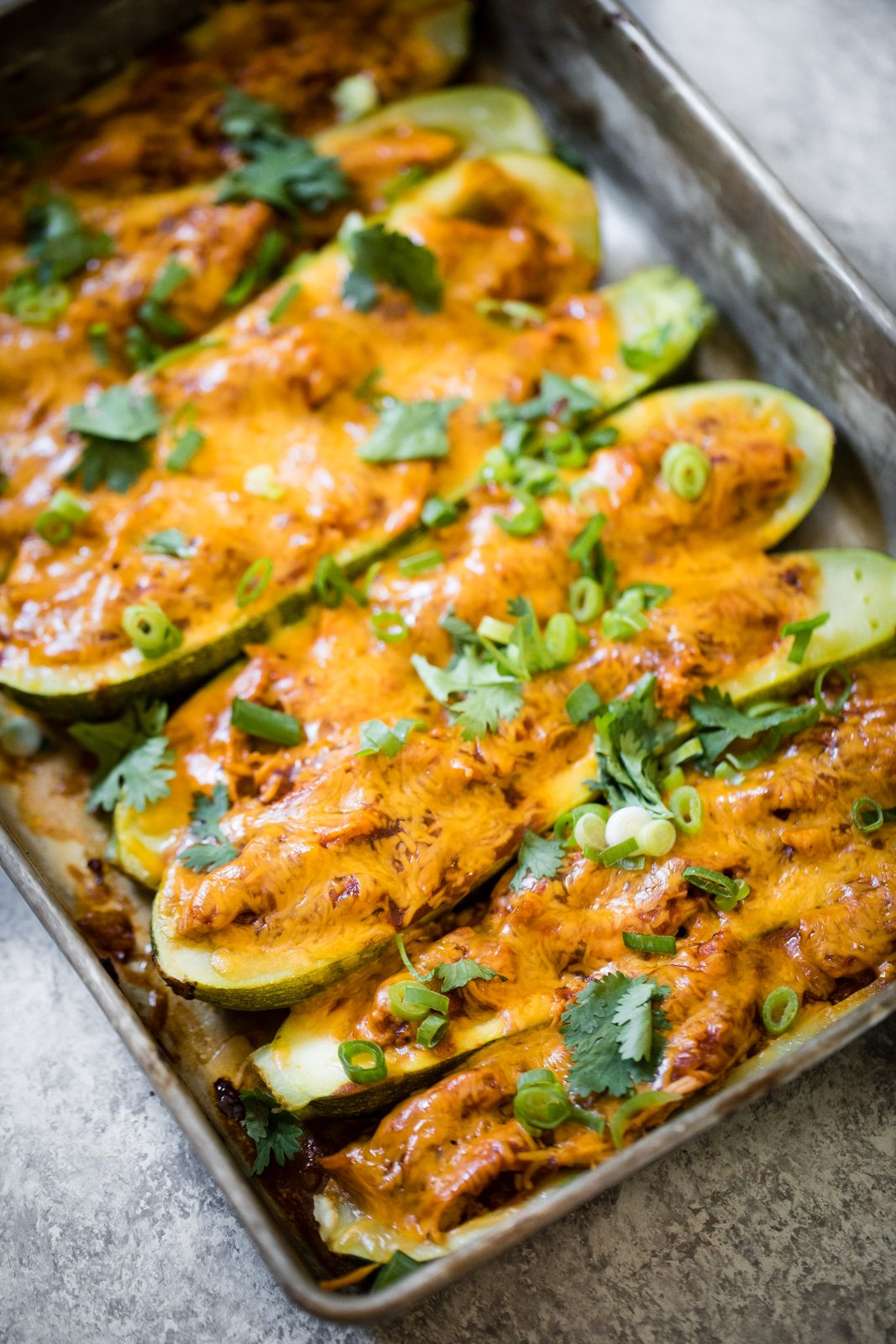 bbq chicken stuffed zucchini boats in a baking pan