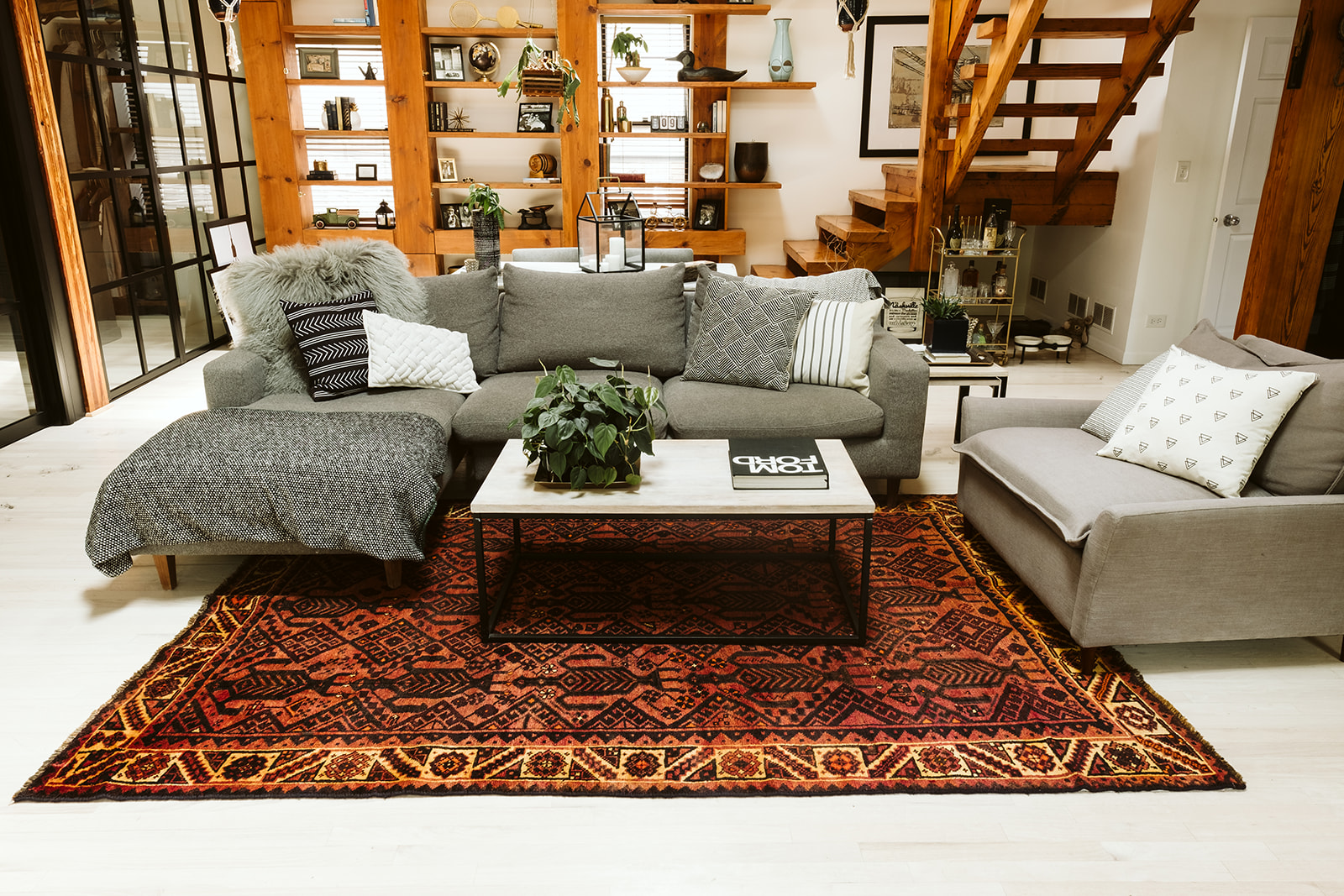 living room with an orange and yellow rug and a grey couch