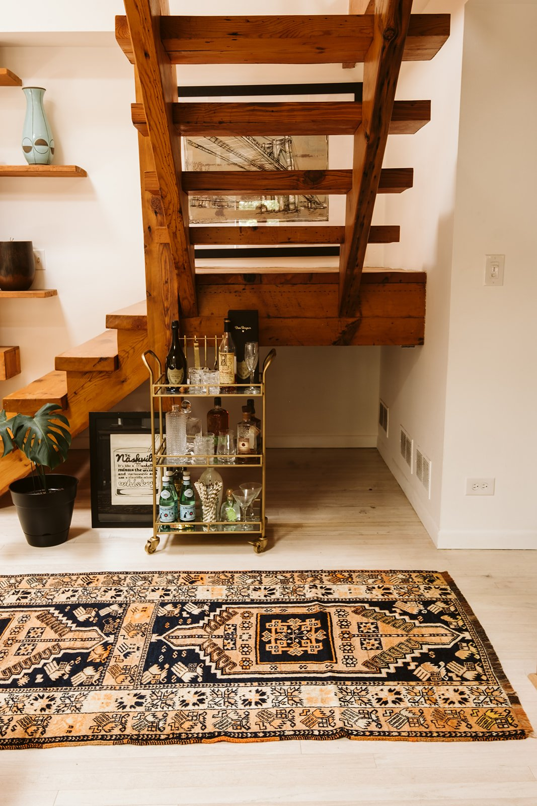 vintage rug next to a bar car under a wooden staircase