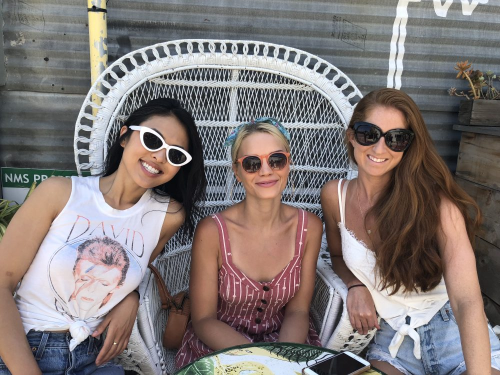 three girls with sunglasses sitting on white chairs