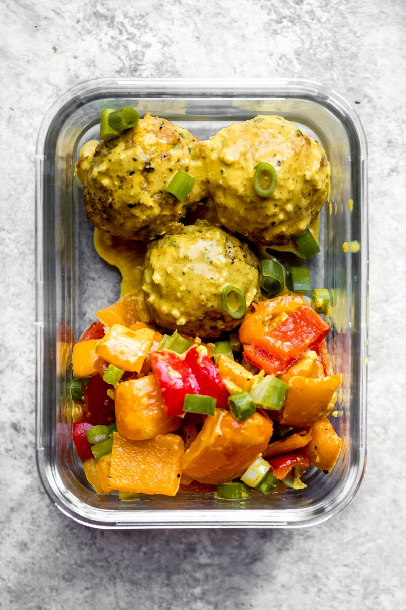 healthy zucchini chicken meatballs in a glass container with bell peppers