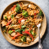 spicy thai peanut chicken stir fry on a plate with a fork