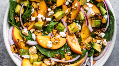 peach spinach salad with avocado and feta in a bowl