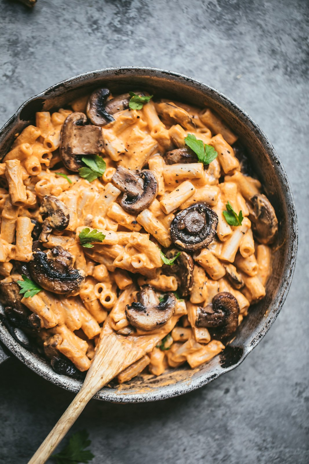 sweet potato penne pasta with vegan sweet potato cream sauce in a skillet with mushrooms and a wooden spoon