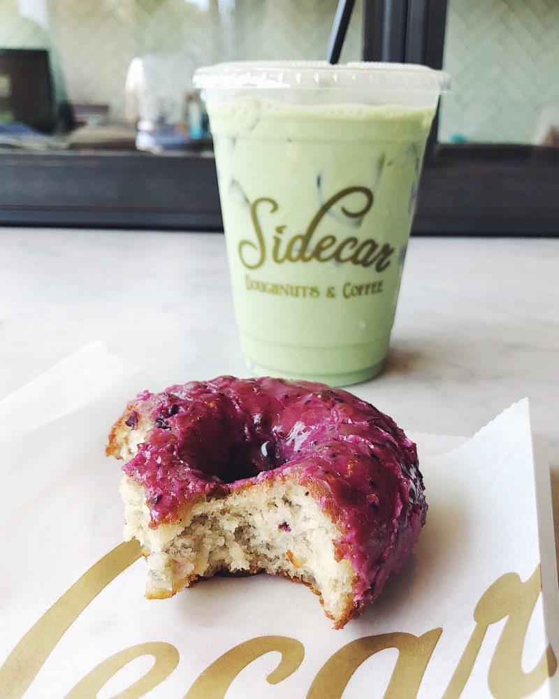 blueberry donut with a green latte in the background