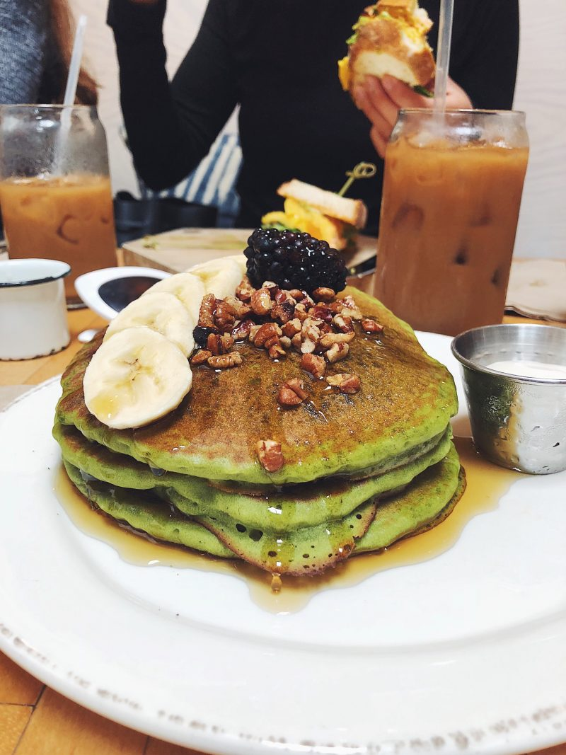 green pancakes topped with bananas and walnuts on a plate