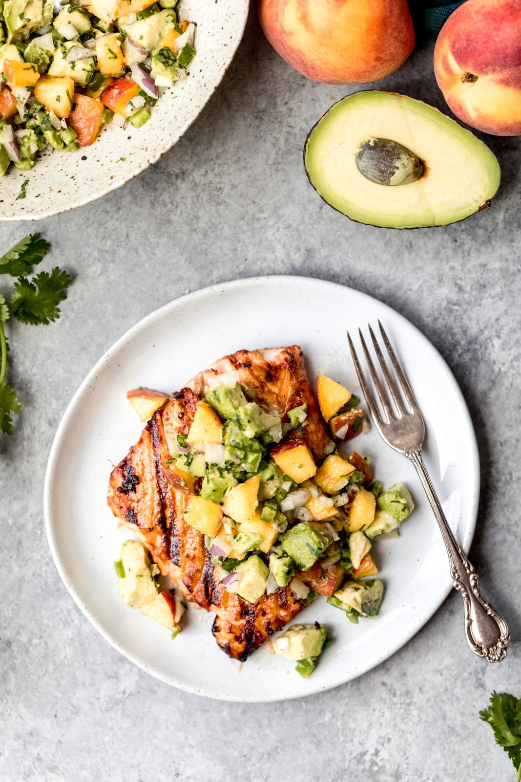 firecracker salmon topped with peach avocado salsa on a plate with a fork next to half of an avocado and two peaches