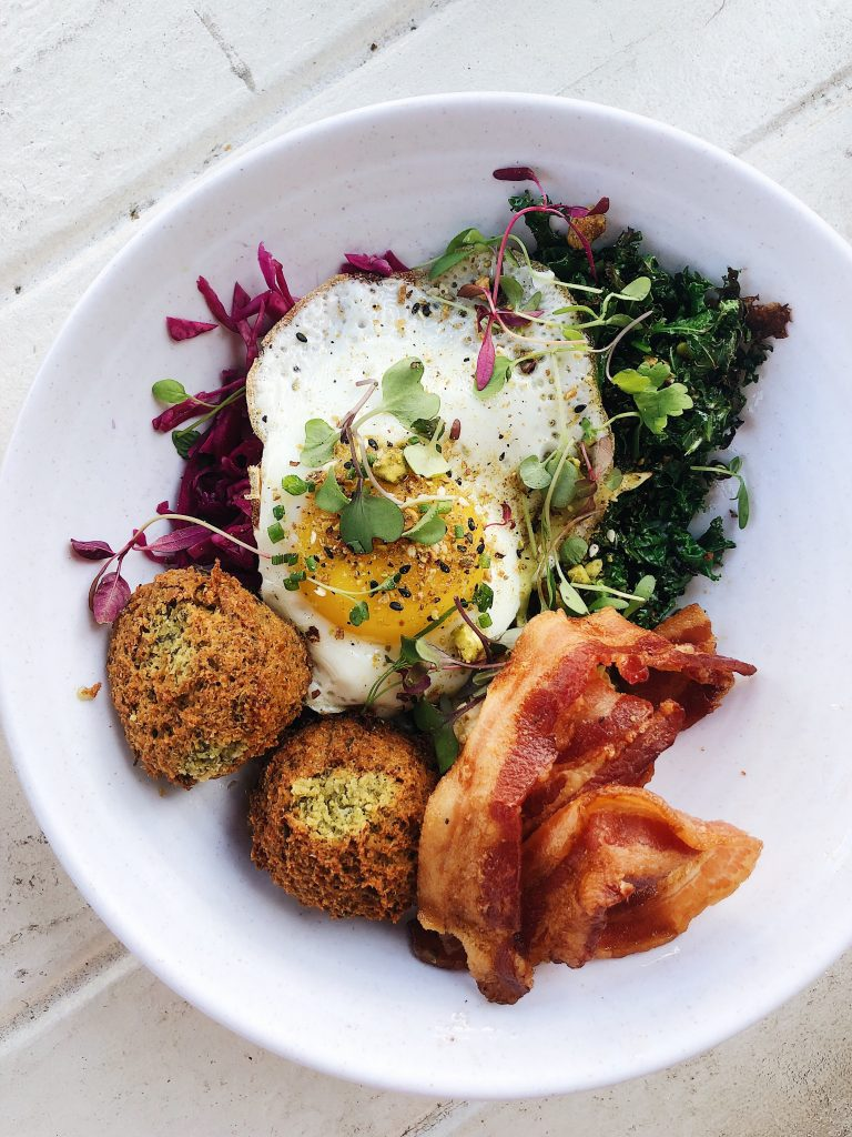 eggs, bacon, greens, and falafel on a plate