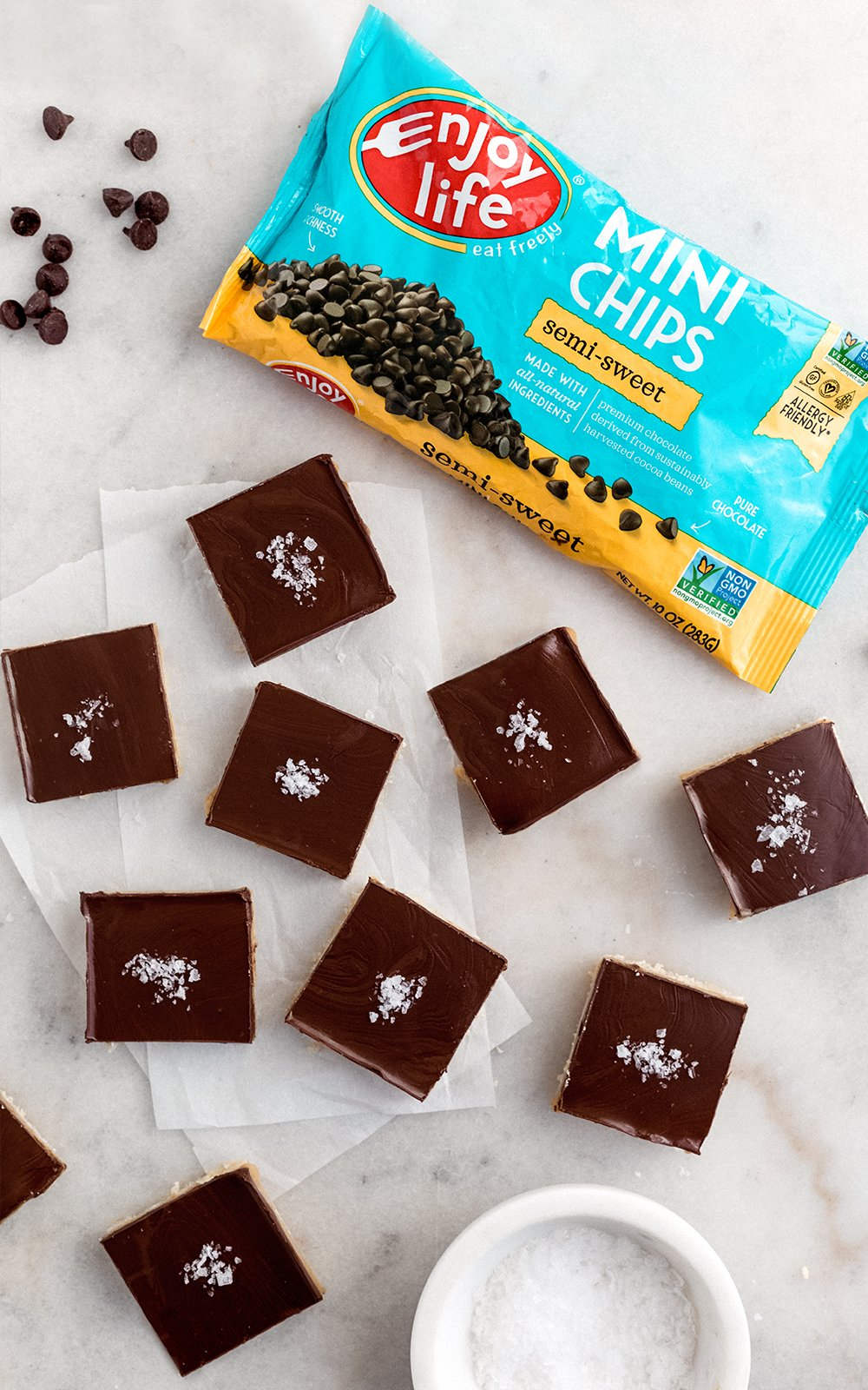 Easy to make millionaire bars with a shortbread cookie base, salted tahini caramel filling and topped with dairy free chocolate. Both vegan, gluten free and paleo! This recipe is in partnership with Enjoy Life.