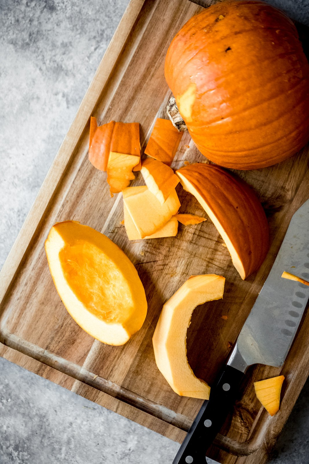pumpkin cut into pieces on a cutting board with a knife