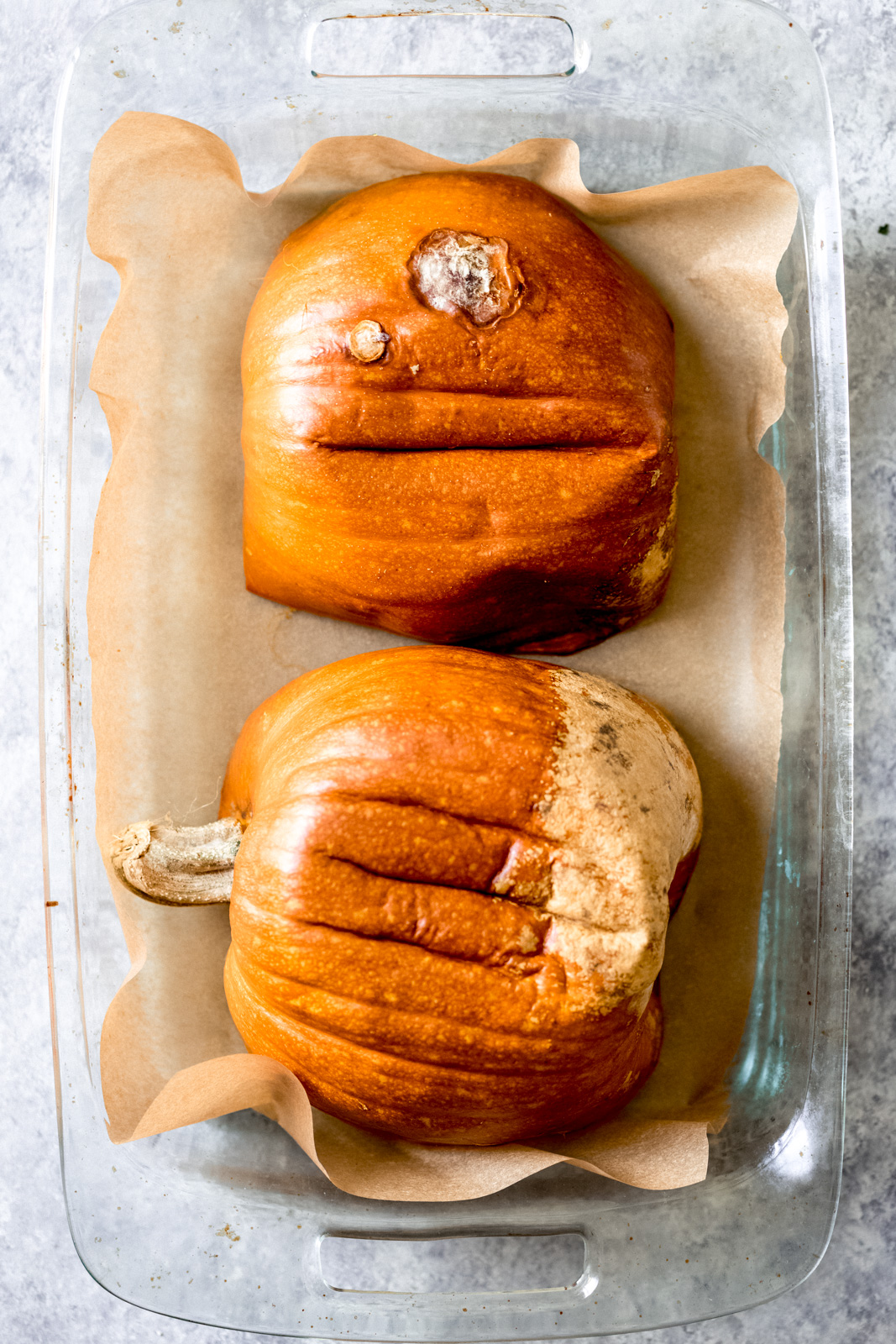 two pumpkin halves face down in a glass baking pan