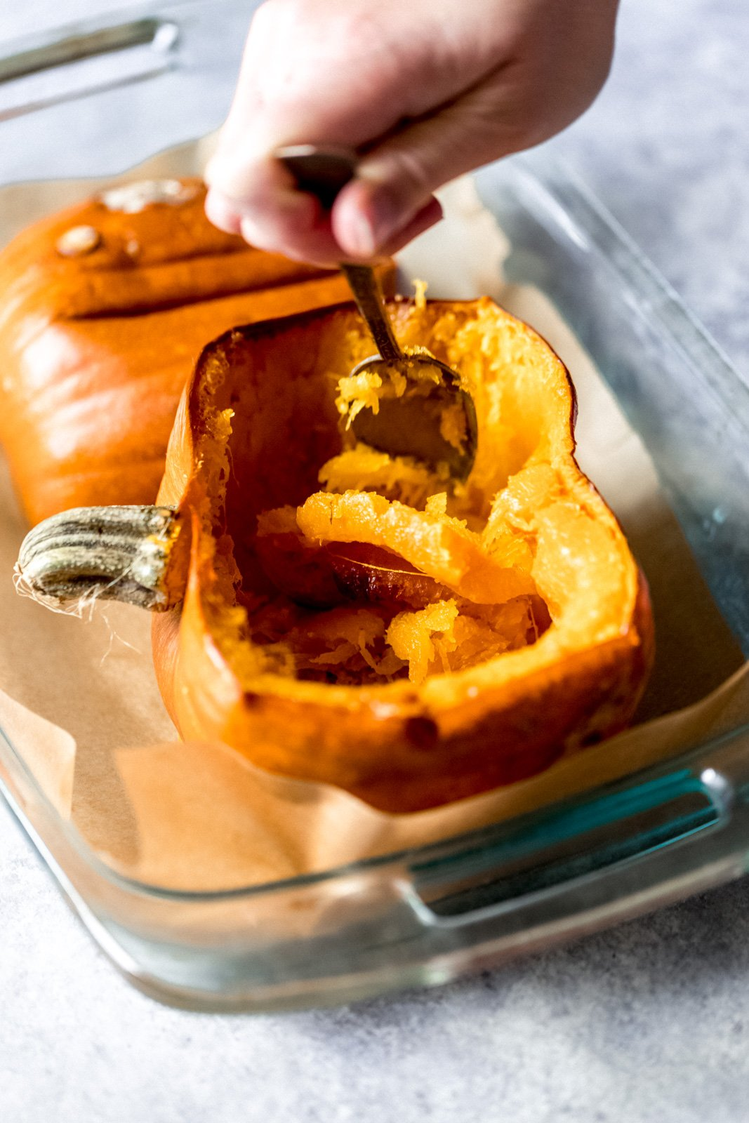 hand scooping out the inside of half of a cooked pumpkin in a glass baking dish