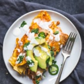 chicken pumpkin enchiladas on a plate topped with avocado