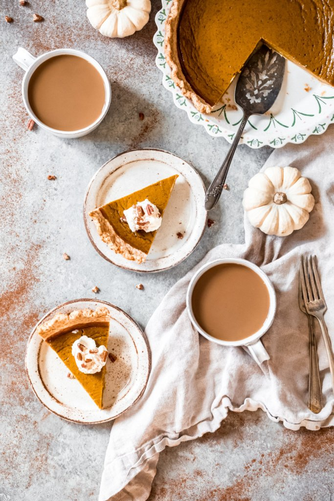 healthy pumpkin pie sliced on plates and in a pie pan