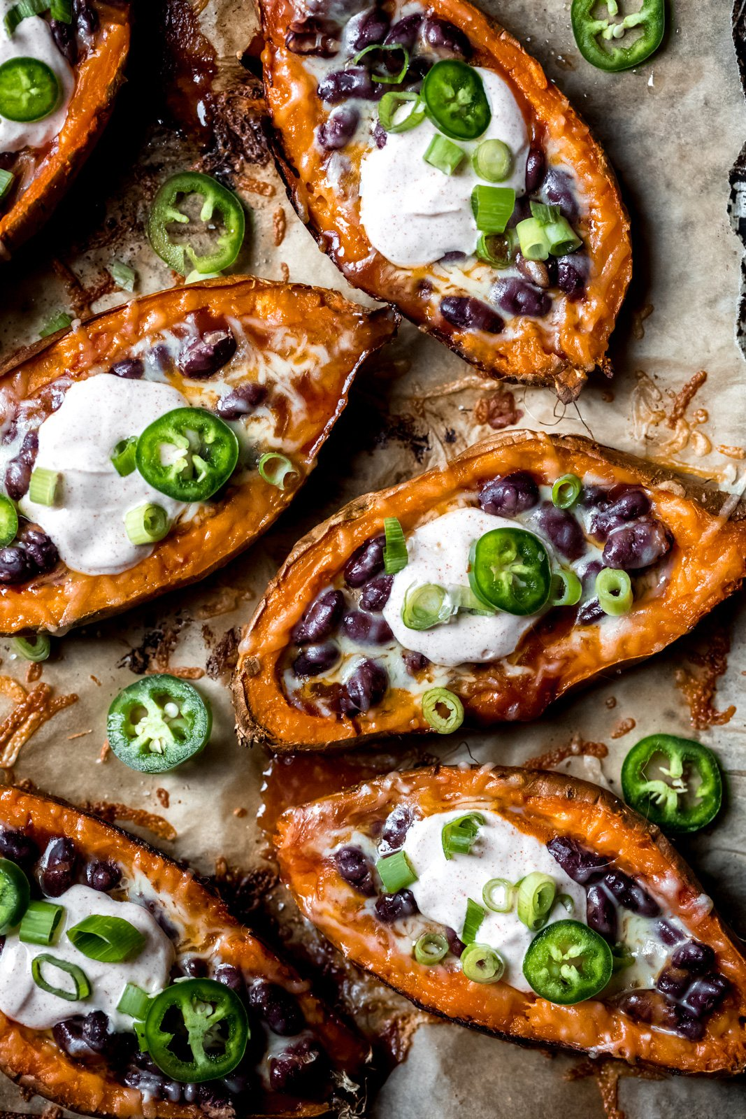 stuffed sweet potato skins topped with jalapeño slices on a baking sheet