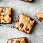 Paleo chocolate chip tahini blondies on a grey board