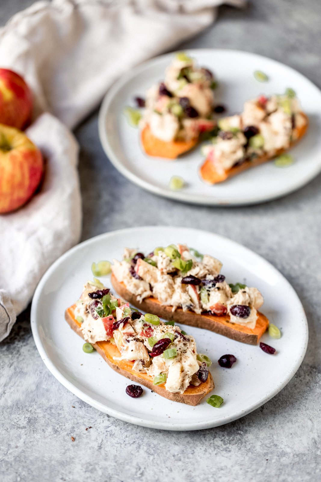 apple tuna salad on top of two pieces of sweet potato toast on two plates