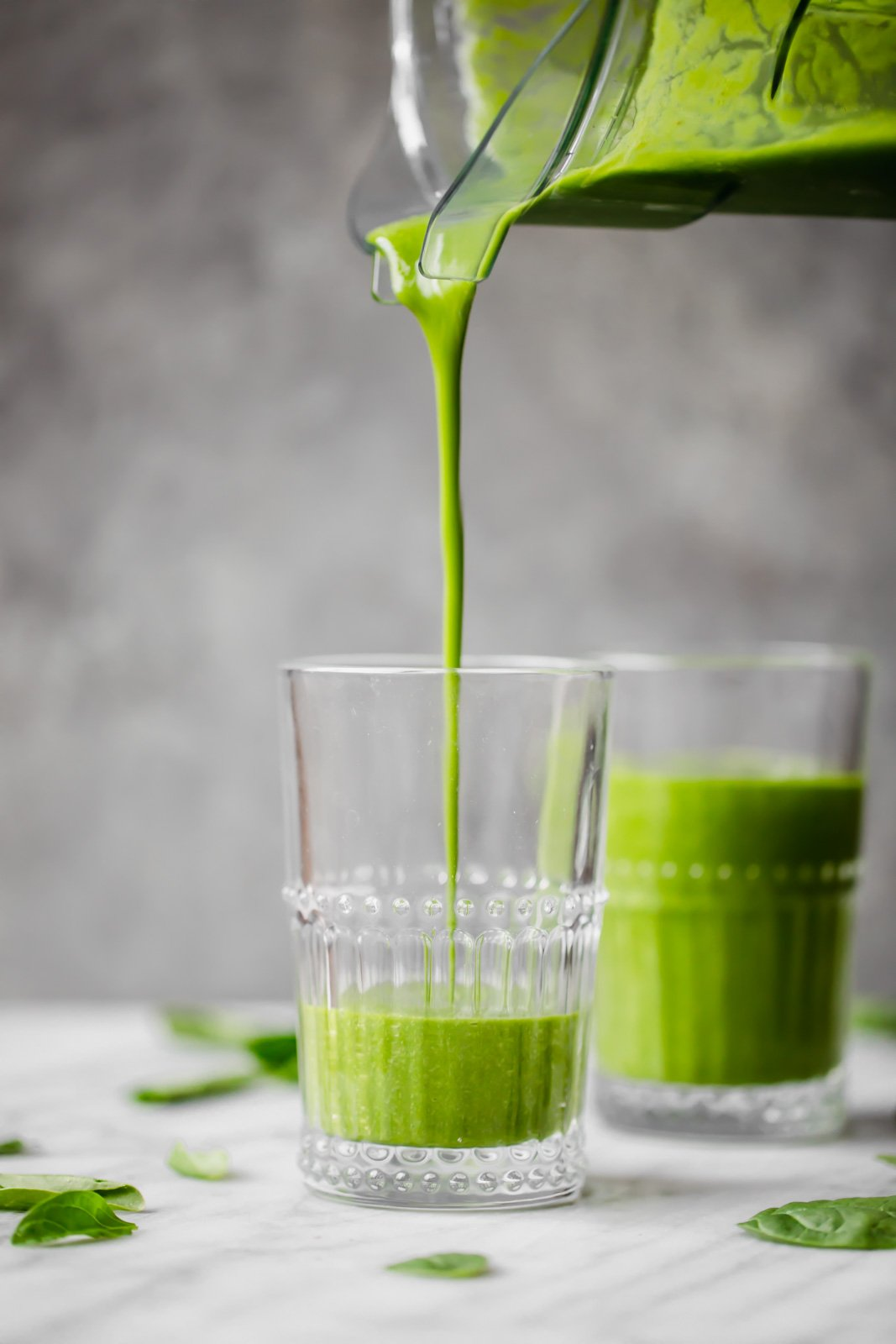pouring a green, immune boosting wellness smoothie into a glass