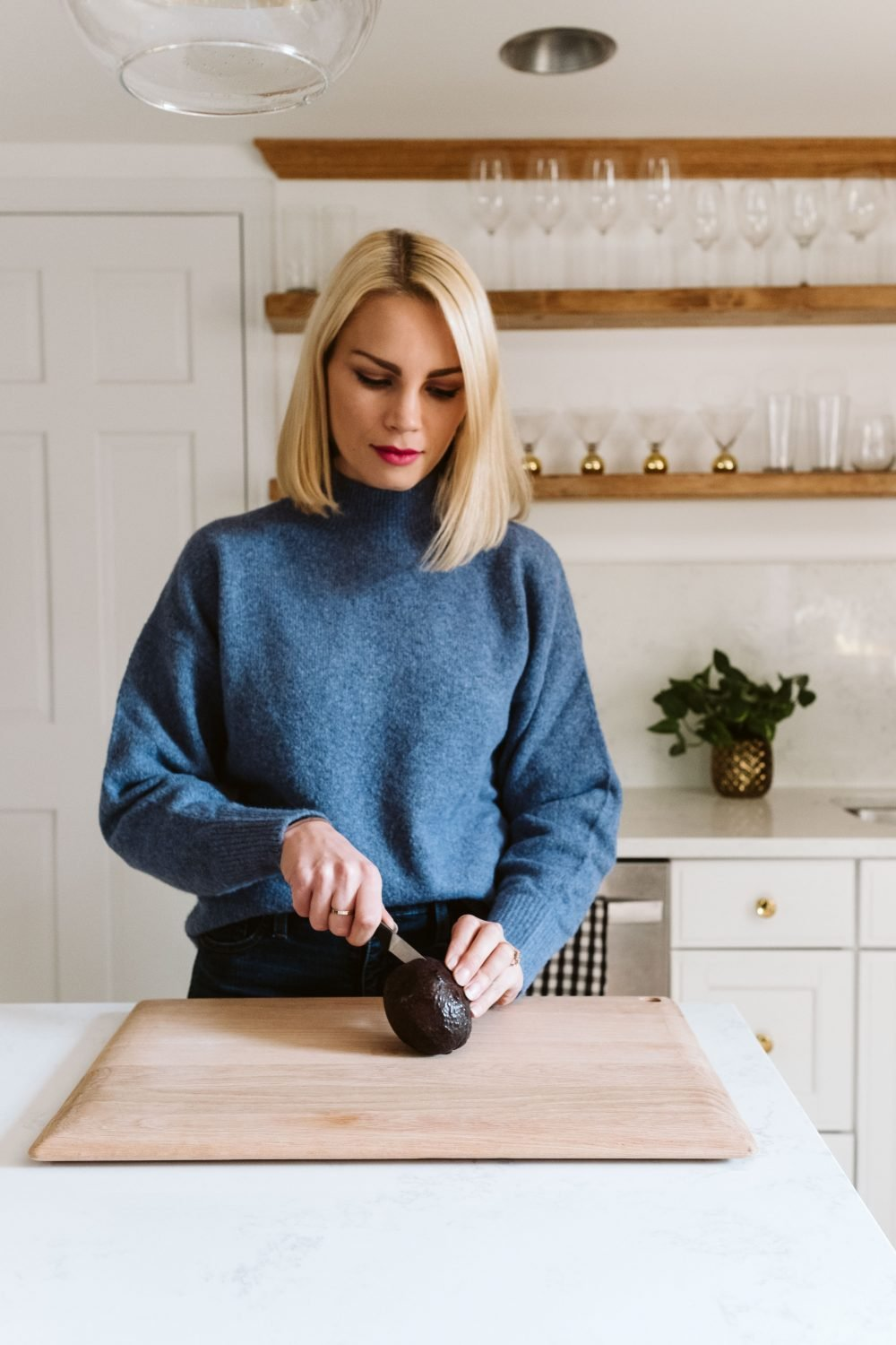 blonde woman demonstrating how to cut an avocado on a wooden board