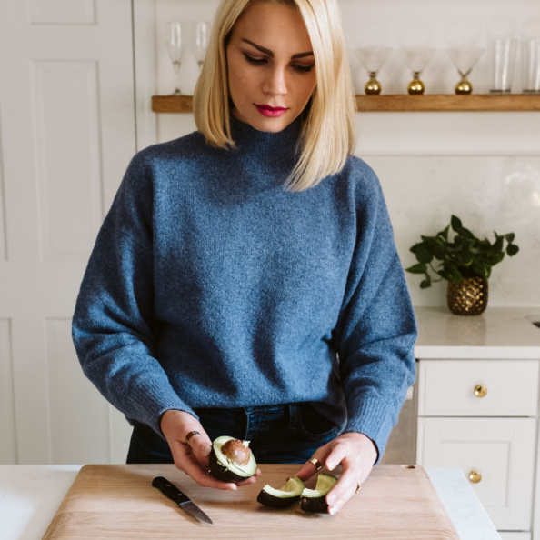 blonde woman demonstrating how to cut an avocado