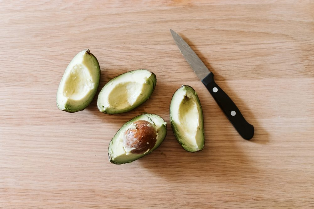 four sections of an avocado on a wooden board with a paring knife