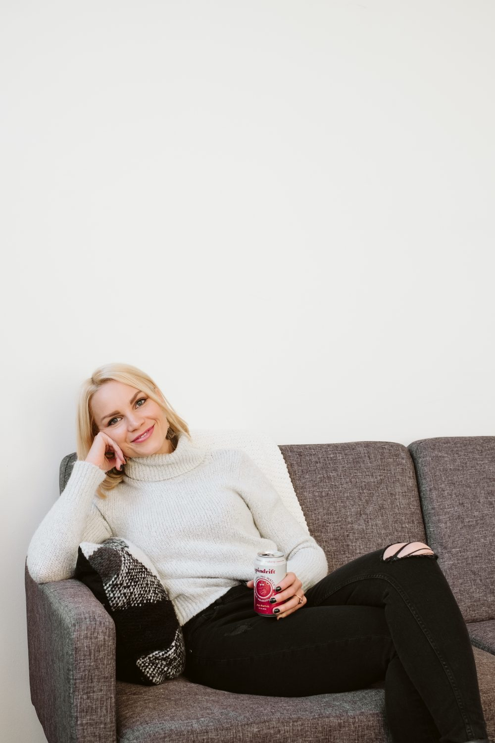 blonde woman sitting on a couch with a can of spindrift sparkling water